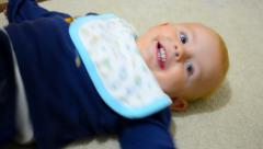 Happy todler child is smiling while mother plays an exercise with his legs Stock Footage