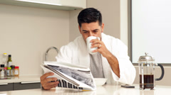Handsome man drinking coffee and reading newspaper Stock Footage