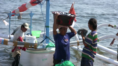 Woman carrying a bucket full of fishes on the head at Amed beach Stock Footage