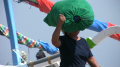 Woman carrying fishing net on the head at Amed beach Stock Footage