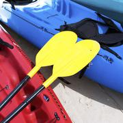 yellow kayak oar on the red kayak - stock photo