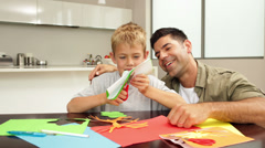Happy father and son doing arts and crafts at kitchen table Stock Footage