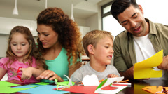 Happy parents and children doing arts and crafts at kitchen table - stock footage