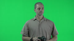 Green screen, man with DSLR camera taking shots following the action Stock Footage