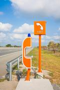 sos sign and phone box on highway, road safety - stock photo