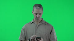 Green screen, man dials smartphone, good conservation looks at watch Stock Footage