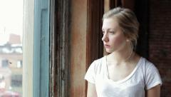 Camera Pans Right To Reveal Sad Young Woman Looking Out Window Stock Footage