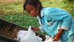 Little girl looking in a trash food Stock Footage