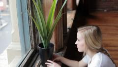 Young Woman Decorates Her Home, Places Plant In Window And Smiles Stock Footage
