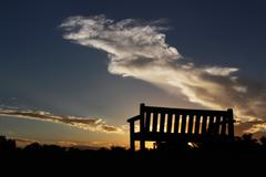 park bench silhouetted against a cloudy sunset - stock photo