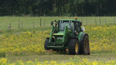 Tractor with mulching attachment clearing land from invasive Ragwort + zoom out Stock Footage
