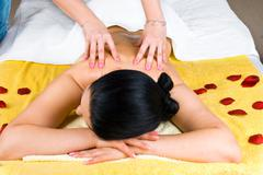 Woman back massaging with oil at spa - stock photo