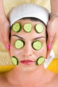 Woman with cucumber slice facial  mask at spa - stock photo