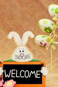 easter smiling bunny with sign welcome - stock photo