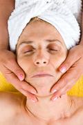 Senior woman receiving a facial massage - stock photo