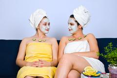 Two women with facial mask at spa salon - stock photo