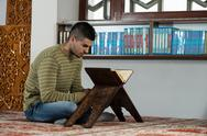 Stock Photo of arabic muslim man reading holy islamic book koran