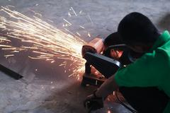 Stock Photo of worker cutting steel and spark