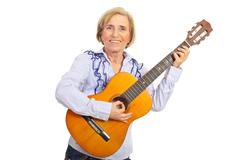 Smiling aged woman with acoustic guitar Stock Photos