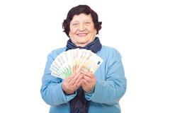 Happy older woman holding Euro banknotes - stock photo