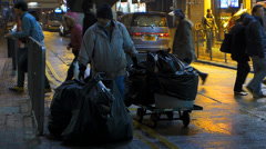 Street cleaner moving garbage to cart downtown Hong Kong China Asia Stock Footage