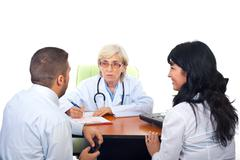 Doctor having conversation with young couple - stock photo