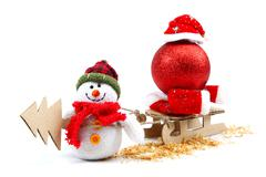 Snowman with sledge, christmas tree, red ball and santa claus hat. Stock Photos