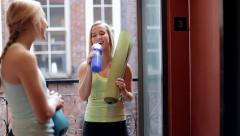 Fit Teens Talk Before Or After Yoga, Wait For Elevator, One Girl Drinks Water Stock Footage