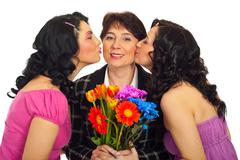 Daughters kissing mother - stock photo