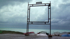 Sea, boat and clouds through an abandoned placard frame Stock Footage