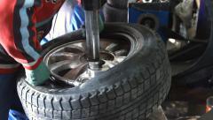 Mechanic removes car tire closeup Stock Footage