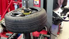 Tyre fitting shop. Worker remove the tire Stock Footage
