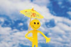 Smilie with yellow parasol enjoying summer sun - stock photo