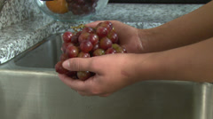 Hands washing grapes over sink Stock Footage