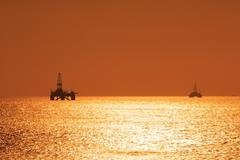 Two offshore oil rigs during sunset in Caspian se Stock Photos