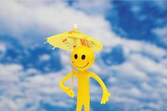 Smilie with yellow parasol  enjoying summer sun Stock Photos