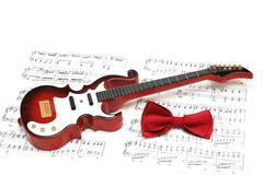 Musical notes, guitar and bow tie on white - stock photo