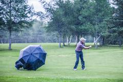 golfer on a rainy day swigning in the fairway - stock photo