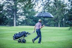 Golfer on a rainy day leaving the golf course Stock Photos