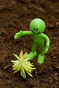 Gardening concept - Smilie looking  after green seedlings - stock photo