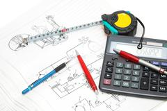 Design drawings, calculator, pens and measuring tape Stock Photos