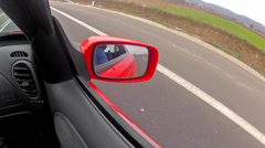reflection in a rearview mirror, fast sport moving car. - stock footage