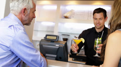 Bartender serving cocktails and chatting to customers Stock Footage