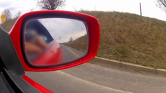car view from the side mirror of a fast red sport moving vehicle. - stock footage
