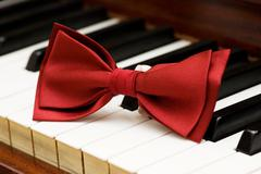 Red bow tie on the piano keys Stock Photos