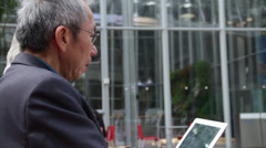 Two Asian Men Looking at an Ipad Stock Footage