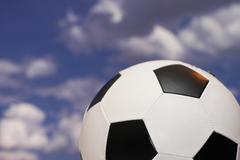 Football with white and black pentagons against sky Stock Photos
