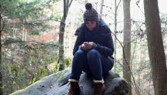 Female sitting in wood texting Stock Footage
