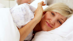 Woman covering her ears as partner is snoring loudly Stock Footage