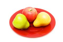 Various fruits and red plate isolated on white Stock Photos